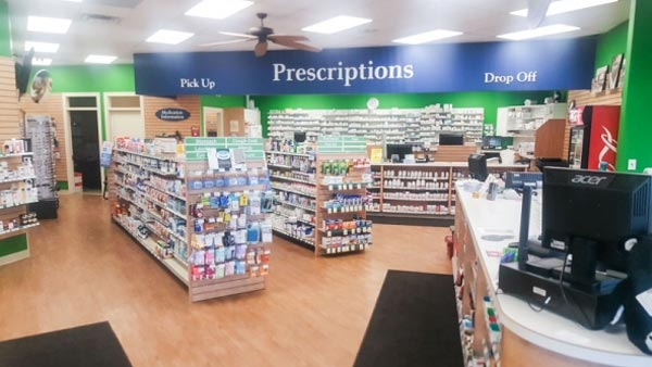 aisles filled with products and the pharmacy counter in a pharmacy store