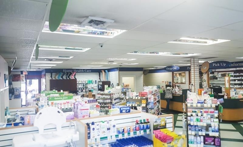 aisles filled with products in a pharmacy store with a pharmacy counter